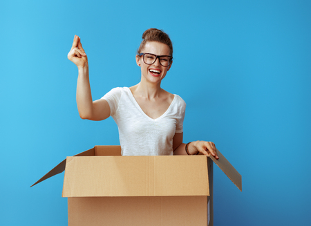 Photo pour happy modern woman in white t-shirt with fingers snapping in a cardboard box isolated on blue background - image libre de droit