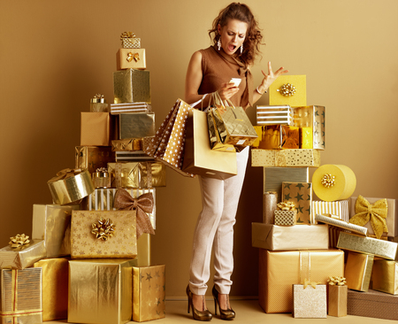 Photo for Full length portrait of annoyed modern fashion-monger in gold beige pants and brown blouse with shopping bags looking at smartphone among 2 piles of golden gifts. stressing while planing party concept. - Royalty Free Image