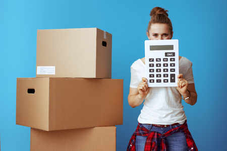 Photo for modern woman in white t-shirt near cardboard box hiding behind calculator isolated on blue background. Moving on budget. - Royalty Free Image