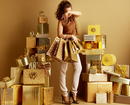 Photo for Stressed modern shopper woman in gold beige pants and brown blouse with shopping bags and smartphone among 2 piles of golden gifts in front of a plain wall. stressing while planing party concept. - Royalty Free Image