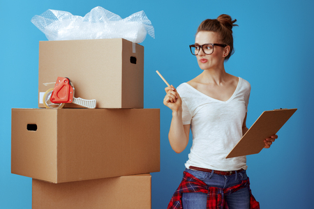Photo pour modern woman in white t-shirt near cardboard box using moving checklist and count boxes isolated on blue - image libre de droit