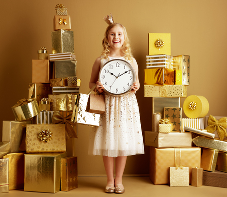 Photo for Full length portrait of happy young girl in beige fit and flare dress and a little crown on head with gold shopping bags and round clock among 2 piles of golden gifts in front of a plain wall. - Royalty Free Image