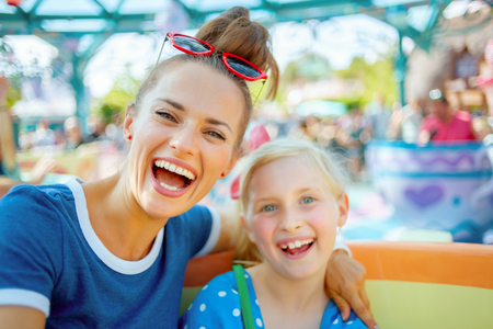 Foto de Portrait of smiling modern mother and child tourists in theme park enjoying attraction. - Imagen libre de derechos