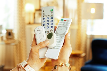 Photo for Closeup on remote controls in hands of modern woman in the living room. - Royalty Free Image