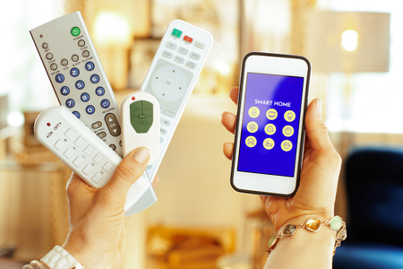 Photo for Closeup on remote controls in one hand and smartphone with smart home application in another hand of modern housewife at home. - Royalty Free Image