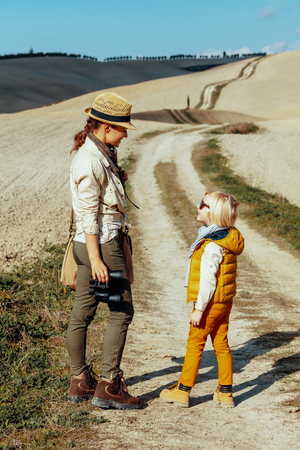 Foto de Full length portrait of happy fit mother and daughter with binoculars looking at each other on summer Tuscany trip. - Imagen libre de derechos