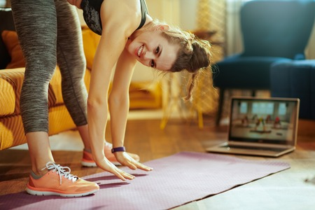 Photo pour smiling young sports woman in sport clothes at modern home using laptop to watch fitness streaming on internet while doing stretching on fitness mat. - image libre de droit