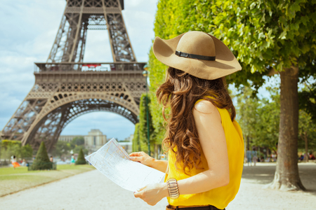 Foto de Seen from behind elegant traveller woman in yellow blouse and hat with map having excursion against clear view of the Eiffel Tower in Paris, France. - Imagen libre de derechos