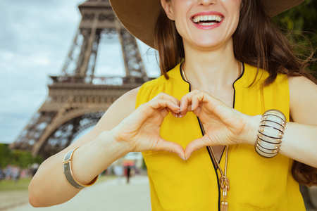 Foto de Closeup on happy modern traveller woman in yellow blouse and hat showing heart shaped hands against Eiffel tower in Paris, France. - Imagen libre de derechos