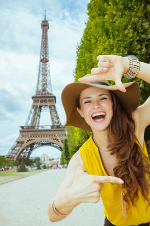 Foto de smiling modern woman in yellow blouse and hat framing with hands in the front of Eiffel tower in Paris, France. - Imagen libre de derechos