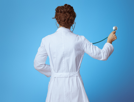 Photo for Seen from behind modern medical doctor woman in bue shirt, red pants and white medical robe listening with stethoscope against blue background. - Royalty Free Image