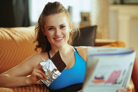 Foto de smiling active woman in fitness clothes in the modern house reading magazine and eating chocolate. - Imagen libre de derechos