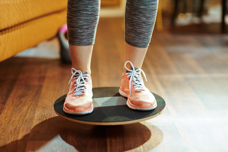 Photo for Closeup on fit sports woman in fitness clothes at modern home while training using balance board. - Royalty Free Image
