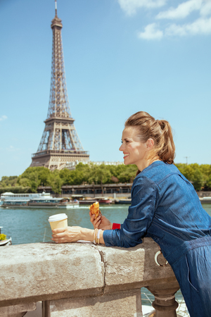 Photo pour smiling young tourist woman in blue jeans overall with cup of coffee and croissant exploring attractions not far from Eiffel tower in Paris, France. - image libre de droit