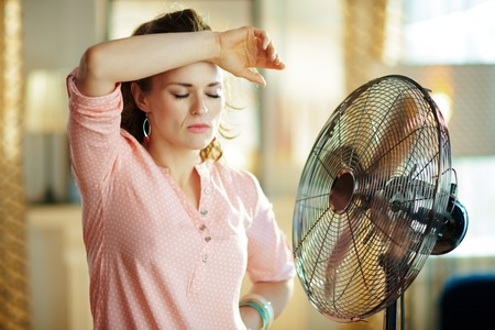Photo for sad stylish housewife in the modern living room in sunny hot summer day exhausted from summer heat while standing in the front of fan. - Royalty Free Image