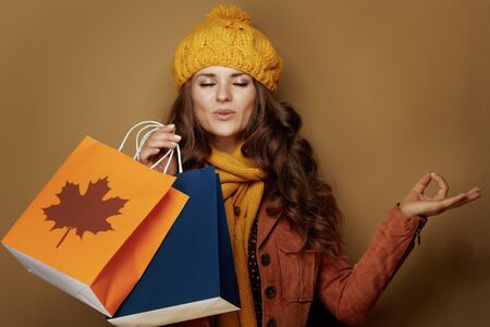 Foto de relaxed young woman in yellow beret and scarf with autumn shopping bags meditating isolated on beige background. - Imagen libre de derechos