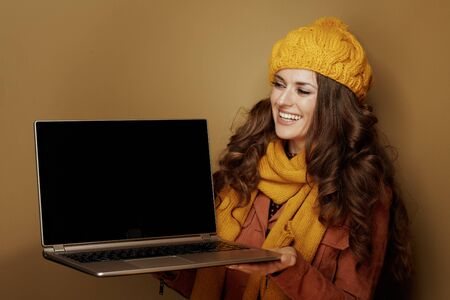 Photo pour happy young woman in yellow beret and scarf looking at laptop blank screen isolated on bronze background. - image libre de droit