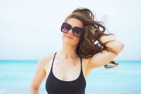 Photo for Portrait of relaxed modern middle age woman in sunglasses with long curly hair in elegant black swimsuit on a white beach. - Royalty Free Image