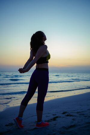 Foto de Seen from behind fit woman in sport clothes on the seashore in the evening stretching. - Imagen libre de derechos