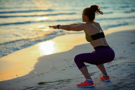 Foto de Seen from behind young sports woman in sport clothes on the beach in the evening doing squats. - Imagen libre de derechos