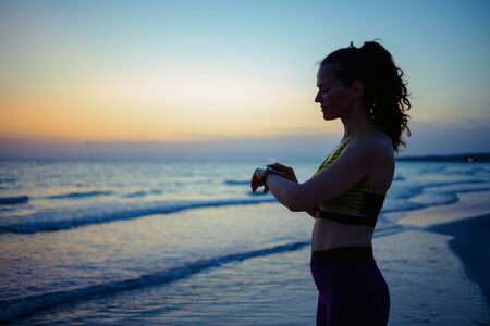Foto de Silhouette of healthy sports woman in fitness clothes on the ocean coast in the evening using smart watch to share workout results in social media. - Imagen libre de derechos