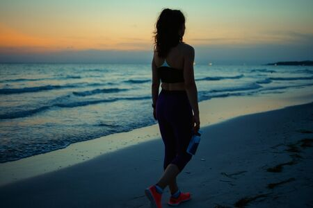Photo for Seen from behind fitness sports woman in fitness clothes with bottle of water walking after workout on the ocean shore in the evening. - Royalty Free Image