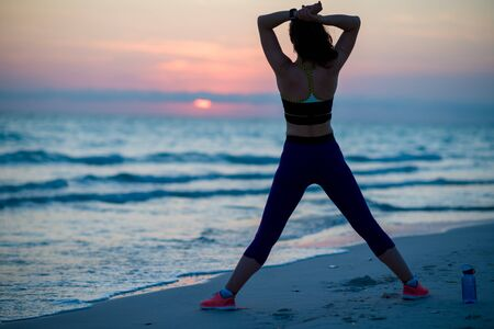 Photo pour Seen from behind fit woman in sport clothes on the seacoast in the evening looking into the distance and relaxing after workout. - image libre de droit
