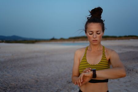 Foto de fitness sports woman in sport style clothes on the beach in the evening using smart watch to track weight in fitness app. - Imagen libre de derechos