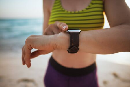 Foto de Closeup on fit woman in sport style clothes on the seacoast at sunset with smart watch using app to track fitness activity. - Imagen libre de derechos