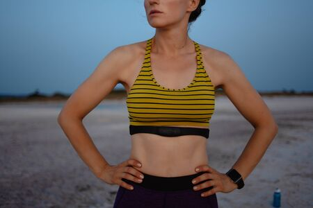 Foto de Closeup on fit sports woman in sport style clothes with heart rate monitor on the ocean shore in the evening. - Imagen libre de derechos