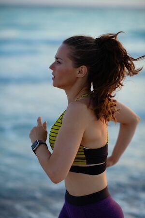 Foto de active sports woman in sport clothes on the seacoast in the evening jogging. - Imagen libre de derechos