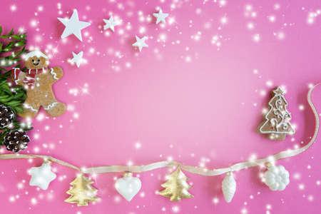 Foto de Christmas decoration with stars, ligths and gingerbread man on pink background, copy space - Imagen libre de derechos