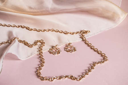 Foto per Luxury gold jewelry chain and earrings on pink background with silk, copy space, selective focus. - Immagine Royalty Free