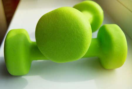 Photo pour Concept of fitness, healthy lifestyle-two green dumbbells for sports, sunlight. - image libre de droit
