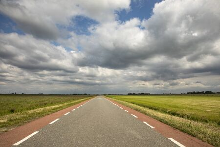 Foto de Road in Holland with red cycle path on both sides, perspective, under heavy dark threatening cloudy skies and between green meadows and a faraway straight horizon. - Imagen libre de derechos