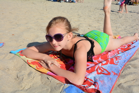 Photo for Girl is lying on the beach - Royalty Free Image