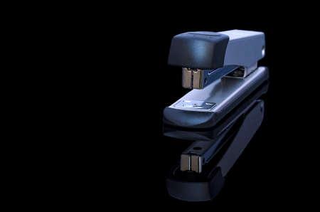 Foto de A metalic stapler on black background - Imagen libre de derechos