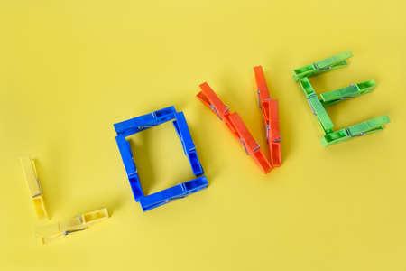 Foto de love message written with clothes pegs on yellow background - Imagen libre de derechos