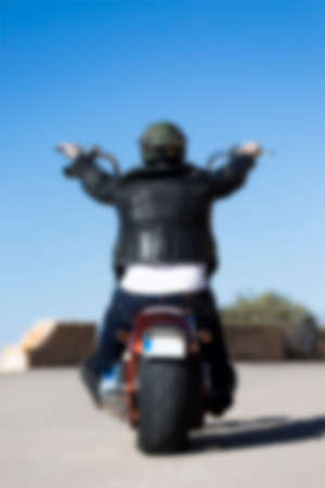 rear view of a chopper motorcyclist riding his customized motorcycle by a mountain road at sunrise unfocused - usefull as background - focus on the head