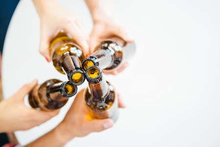 Foto de Unrecognizable company clinking bottles of beer.From above - Imagen libre de derechos