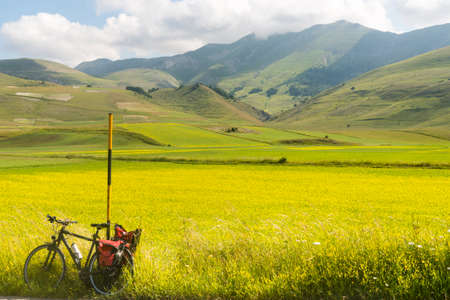 Foto de Piano Grande di Castelluccio (Perugia, Umbria, Italy), famous plateau in the natural park of Monti Sibillini. A bicycle with bags. - Imagen libre de derechos