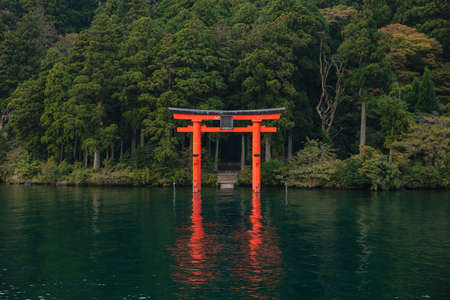 Photo for Red Torii gate submerged in the waters of Ashi lake, caldera with mountains on the background - Royalty Free Image