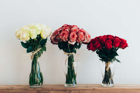 Foto de Bouquets of roses in three glass vases next to a watering can on a white wall - Imagen libre de derechos