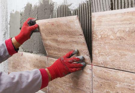 Photo pour Ceramic Tiles. Tiler placing ceramic wall tile in position over adhesive - image libre de droit