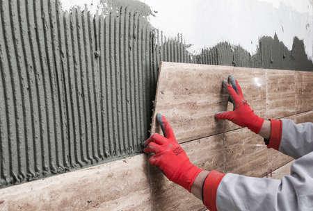 Photo pour Home improvement, renovation - construction worker tiler is tiling, ceramic tile wall adhesive - image libre de droit