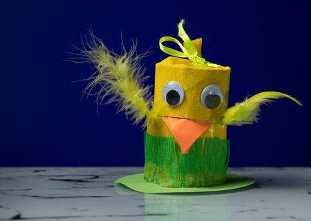 Foto de Closeup of a small yellow chick made of toilet paper roll by a child - Imagen libre de derechos