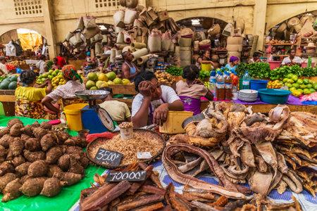 Foto de Hell Ville, Nosy Be, Madagascar - December 27, 2016. Women selling their produce at the central market of Hellville - Imagen libre de derechos