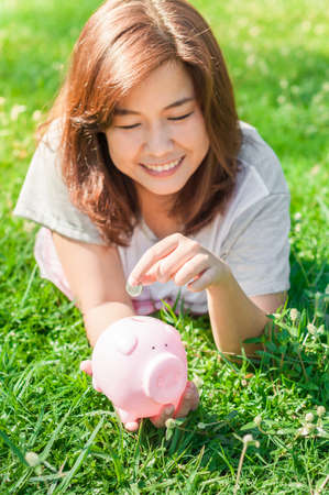Woman Putting Coin In Piggy Bank, Outdoor