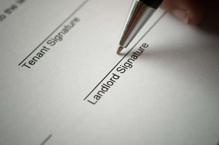 Photo for Rental agreement form with signing hand and pen. - Royalty Free Image
