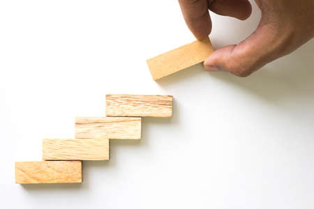 Photo pour Hand aranging wood block stacking as step stair. Business concept for growth success process. - image libre de droit